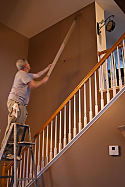 Two Story Room Being Painted And The Use Of A Step Ladder To Reach Upper